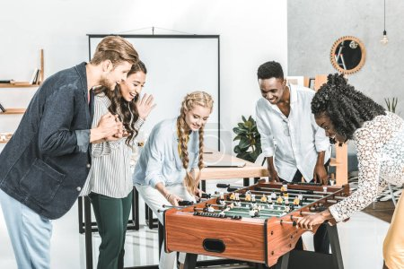 multicultural businessmen and businesswomen playing table football together in office