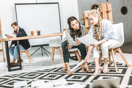 Photo pour Femmes d'affaires songeur multiculturelles faire de la paperasse ensemble et collègue à l'aide de smartphone au bureau - image libre de droit
