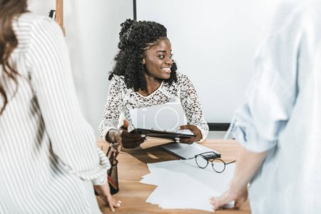 Photo for Portrait of cheerful african american businesswoman during business meeting with colleagues in office - Royalty Free Image