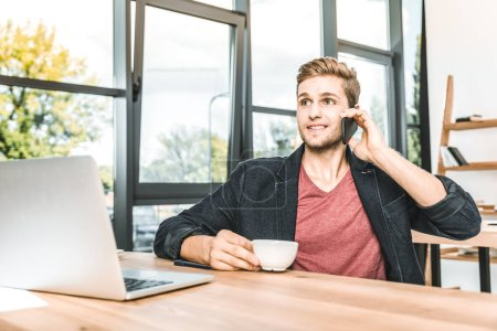 Photo for Portrait of young businessman talking on smartphone at workplace in office - Royalty Free Image