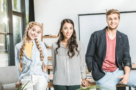portrait of stylish multiethnic business people standing together at workplace in office