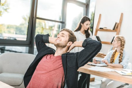 portrait of young businessman relaxing while multiethnic colleagues working together in office