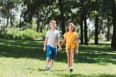beautiful smiling children holding hands and walking together in park