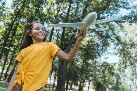 low angle view of cute happy child holding toy plane in park