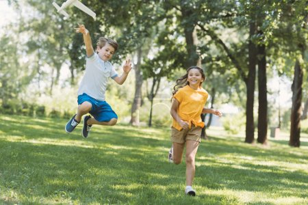 adorable happy children playing with plane model in park
