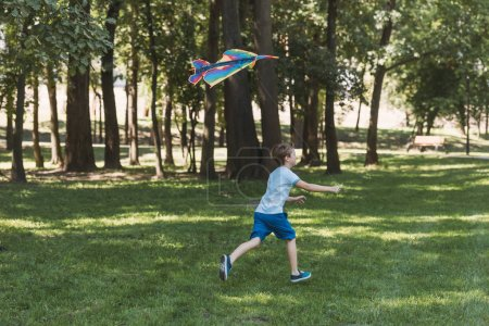 side view of cute little boy playing with colorful kite and running in park