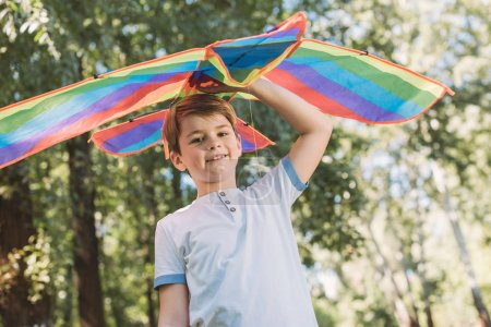 Photo for Low angle view of cute happy boy holding kite and smiling at camera in park - Royalty Free Image