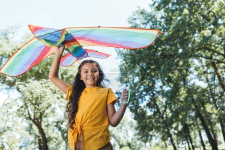 Photo for Low angle view of happy child holding colorful kite and smiling at camera in park - Royalty Free Image