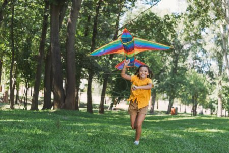Photo for Beautiful happy child holding colorful kite and running in park - Royalty Free Image