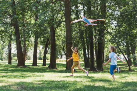 Photo for Cute happy children playing with colorful kite in park - Royalty Free Image
