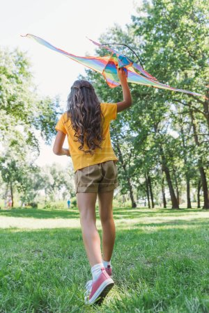 Photo for Back view of cute child playing with colorful kite in park - Royalty Free Image