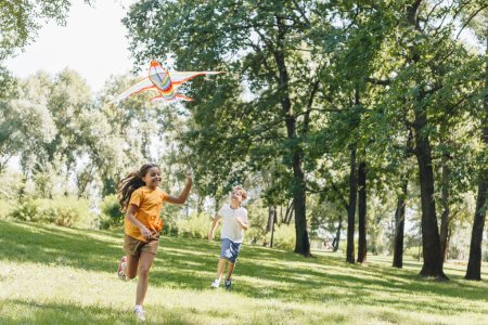 cute happy kids playing with colorful kite in park