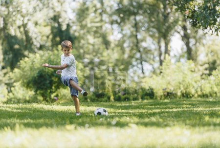 full length view of happy boy playing with soccer ball on grass in park