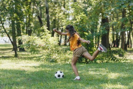 Photo for Side view of child kicking soccer ball in park - Royalty Free Image