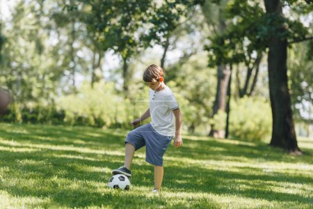 Photo for Full length view of cute little boy playing with soccer ball in park - Royalty Free Image