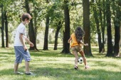 cute little kids playing with soccer ball in park