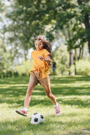 Photo pour Adorable enfant souriant qui joue avec le ballon de soccer dans le parc - image libre de droit