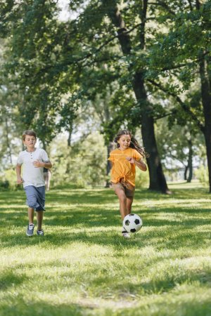 Photo pour Enfants heureux jolis jouant avec ballon de foot dans le parc - image libre de droit