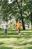 cute happy kids playing with soccer ball in park