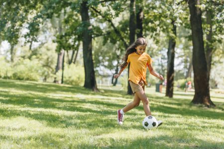 beautiful happy child playing with soccer ball in park