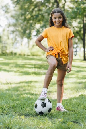 cute happy child standing with soccer ball and smiling at camera in park