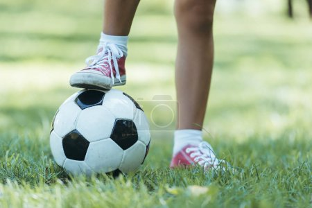 cropped shot of child standing with soccer ball on grass