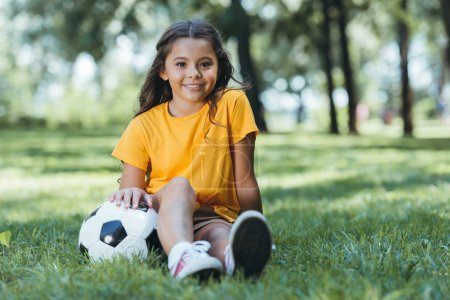 cute happy child sitting on grass with soccer ball and smiling at camera