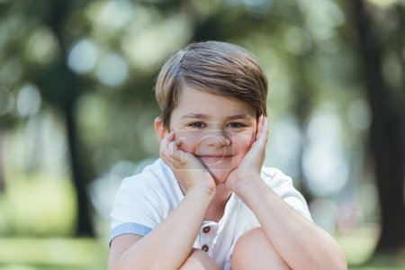 Photo for Portrait of cute happy little boy smiling at camera in park - Royalty Free Image