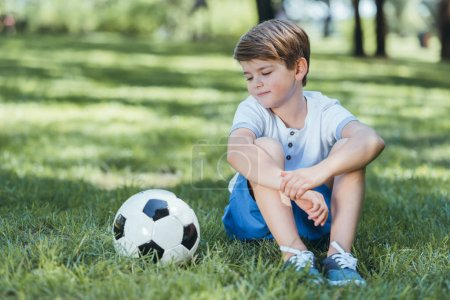 cute little boy sitting on grass and looking at soccer ball