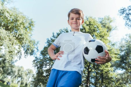 low angle view of boy holding soccer ball and smiling at camera in park