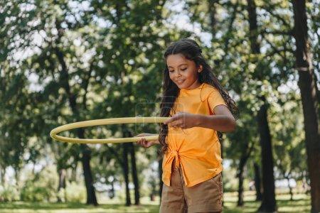 Foto de Hermosa niña feliz jugando con el hula hoop en Parque de - Imagen libre de derechos