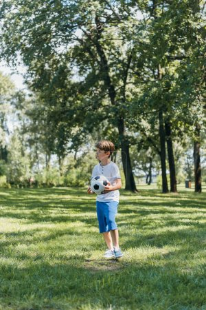 cute little boy holding soccer ball and looking away in park