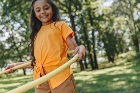 Photo for Cute smiling child playing with hula hoop in park - Royalty Free Image