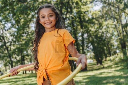 adorable happy child playing with hula hoop and smiling at camera in park