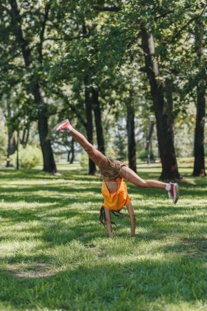 adorable child performing handstand and having fun in park