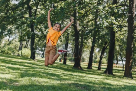 Photo for Cute cheerful kid jumping and smiling at camera in park - Royalty Free Image