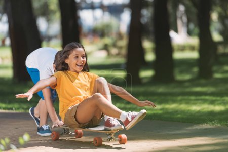 Photo for Adorable happy kids having fun with longboard in park - Royalty Free Image