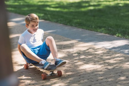 Photo for High angle view of cute smiling boy sitting on skateboard in park - Royalty Free Image