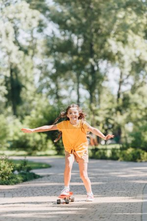 Photo for Beautiful happy kid riding skateboard and smiling at camera in park - Royalty Free Image
