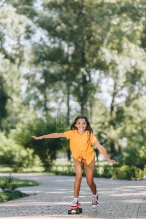 Photo for Cute happy child riding skateboard and smiling at camera in park - Royalty Free Image