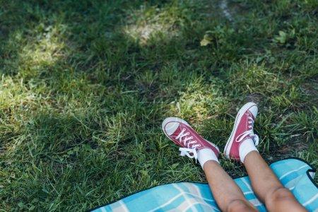 Foto de Sección baja de niño descansando en la hierba verde en el Parque - Imagen libre de derechos
