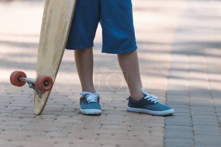 low section of child holding longboard in park