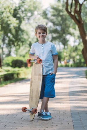 cute happy boy standing with longboard and smiling at camera in park