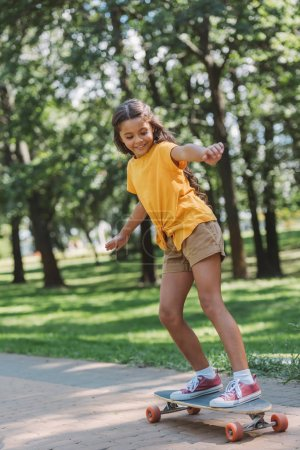 adorable happy child riding skateboard in park
