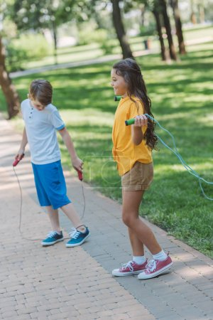 adorable happy kids playing with jumping ropes in park