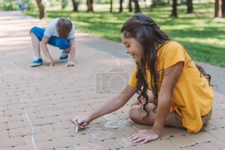 adorable smiling children drawing with chalk in park