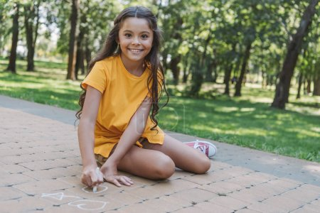 Photo for Beautiful child drawing with chalk and smiling at camera in park - Royalty Free Image