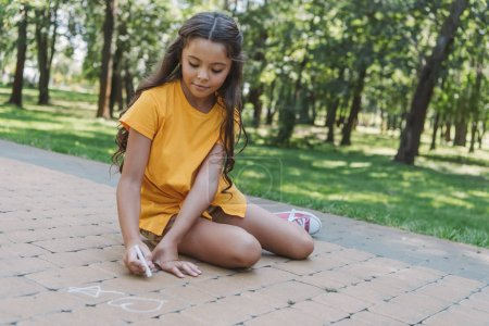 beautiful child sitting and drawing with chalk in park