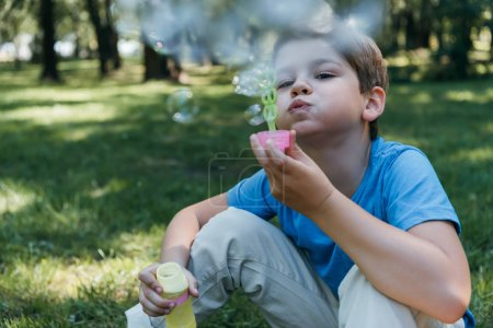 adorable child blowing soap bubbles while sitting on grass in park