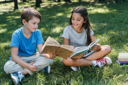 cute little kids sitting on grass and reading books